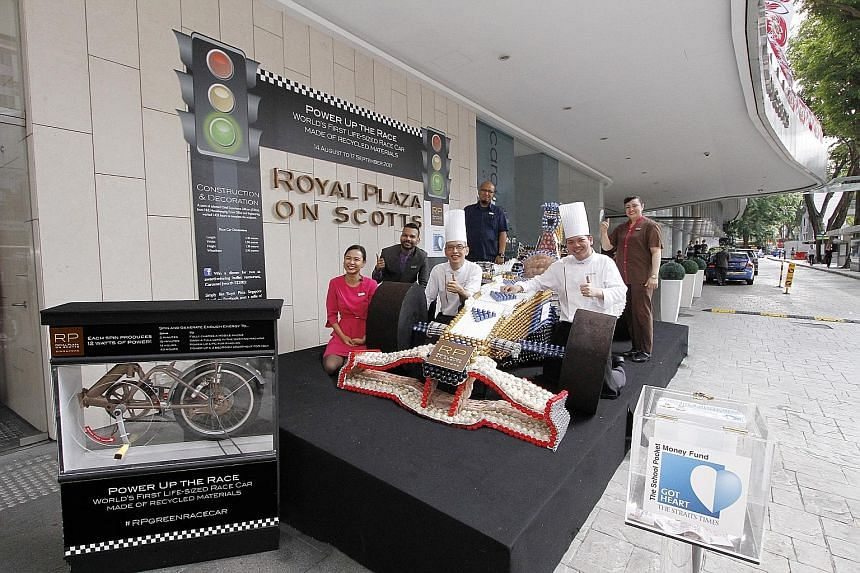 The Royal Plaza on Scotts team behind the life-size race car made from recycled materials. The hotel will match dollar for dollar donations placed in the box for The Straits Times School Pocket Money Fund.