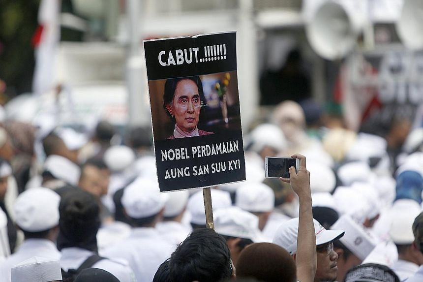 """A protester with a placard that reads """"Pull out the Nobel Peace Prize"""" awarded to Ms Aung San Suu Kyi during a rally against the persecution of the Rohingya in Jakarta yesterday."""