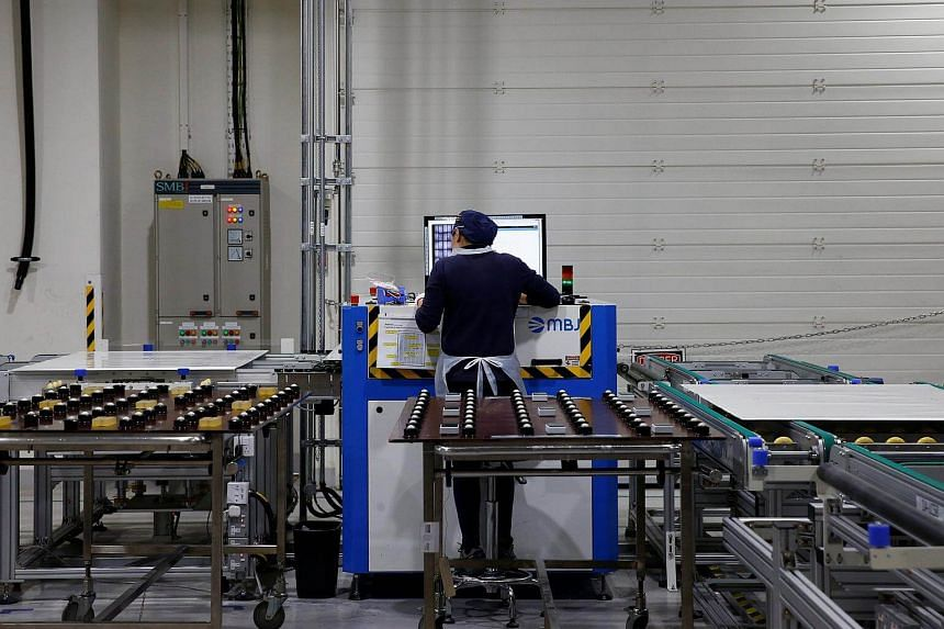 An employee works at a production line at a REC solar panel manufacturing plant in Singapore on May 5, 2017.