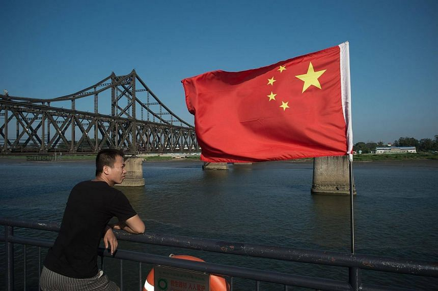 A tourist looking out from the Broken Bridge next to the Friendship bridge (left) on the Yalu River connecting the North Korean town of Sinuiju and the Chinese border city of Dandong on July 6, 2017.