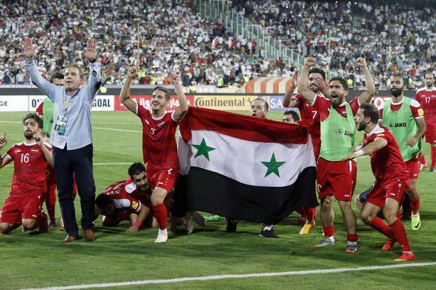 Syria's players celebrate at the end of their Fifa World Cup 2018 qualification football match against Iran on Sept 5, 2017.