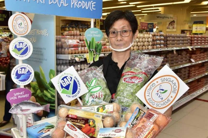 Sales promoter Chris Goh, 56, holds up a basket of local produce.