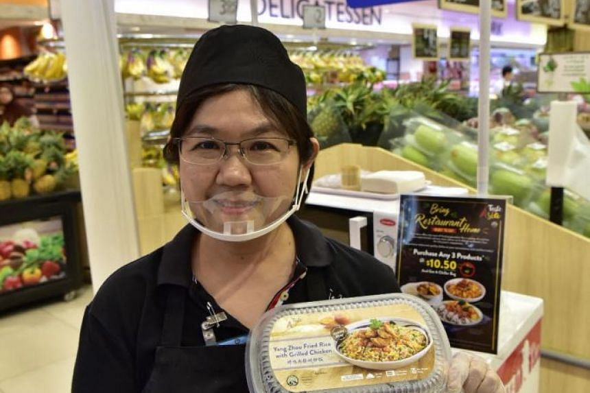 Daphne Lee, 52, sales promoter, holding up a ready-to-eat meal of Yang Zhou Fried Rice with grilled chicken, one of a range of 17 local favourites.