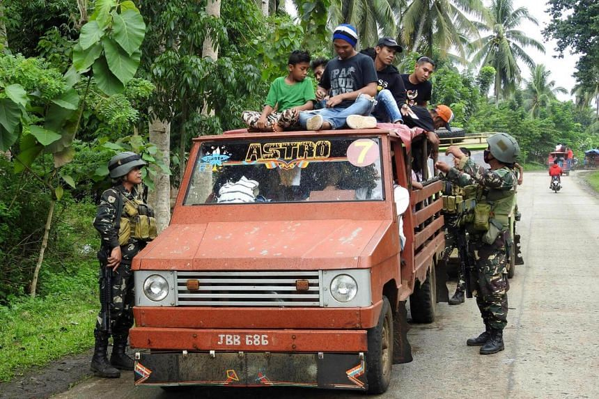 Soldiers inspect a passenger vehicle at a checkpoint in Jolo, Sulu on the southern Philippine Island of Mindanao on July 16, 2017.