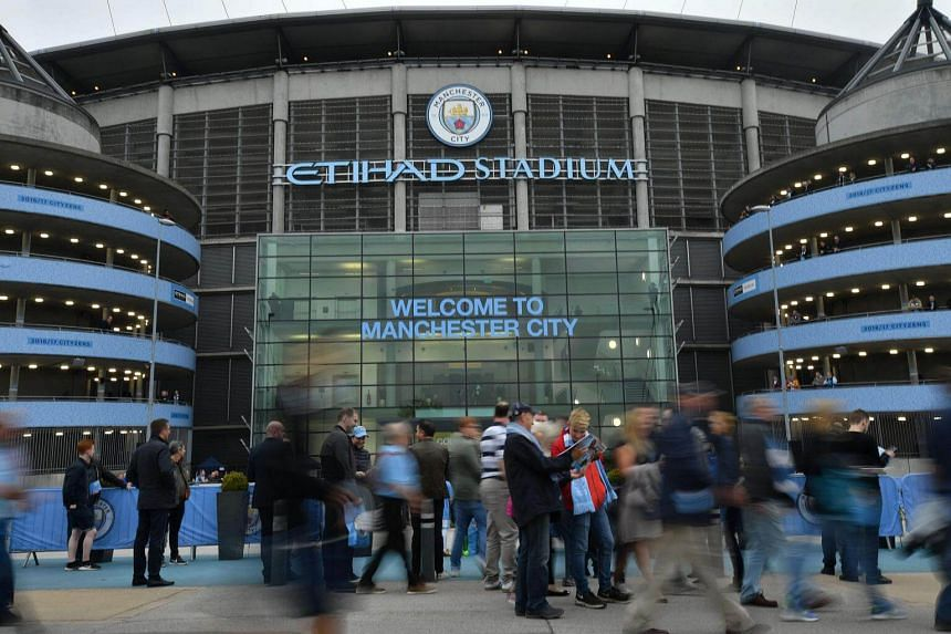 Supporters gather outside the stadium before the English Premier League football match between Manchester City and Everton at the Etihad Stadium in Manchester, north west England, on Aug 21, 2017.