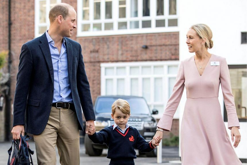 Helen Haslem (right), head of the lower school and Britain's Prince William (left) hold Prince George's hands as he arrives for his first day of school at Thomas's school in Battersea, London, on Sept 7, 2017.