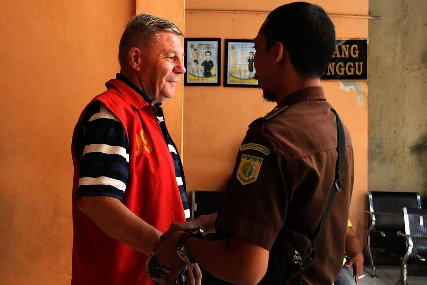 An Indonesian officer removes the handcuffs off Italian Bruno Gallo (left) at a court in Mataram on Sept 7, 2017.