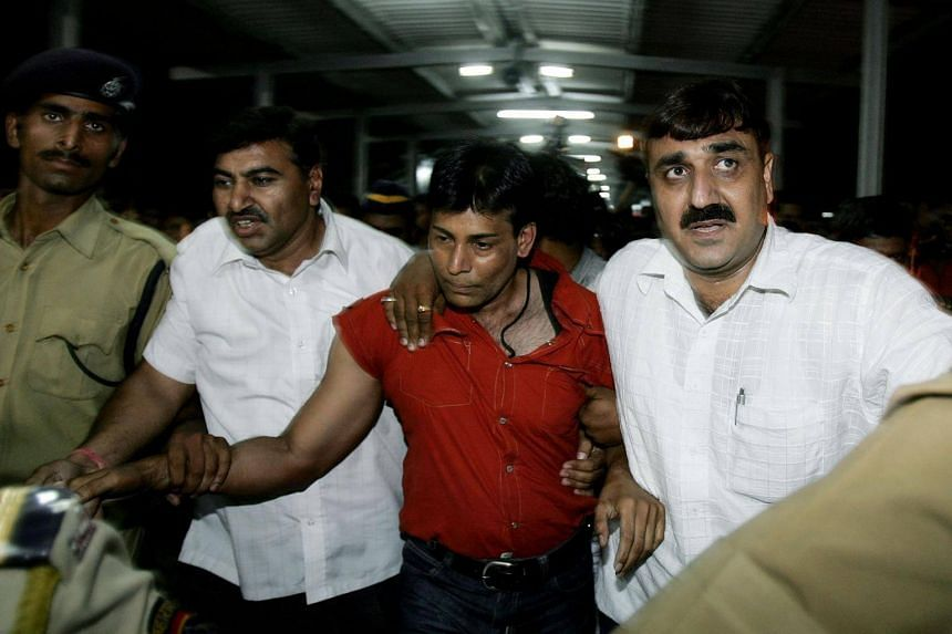 Indian gangster Abu Salem (in the red shirt) being escorted by police personnel at a railway station in New Delhi on May 21, 2017.