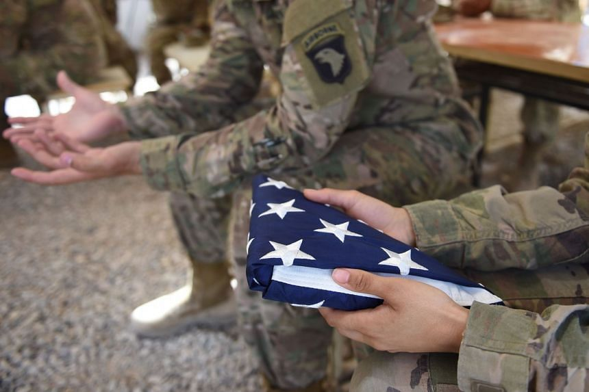 A US soldier holding the national flag ahead of a handover ceremony in the Afghan province of Helmand.