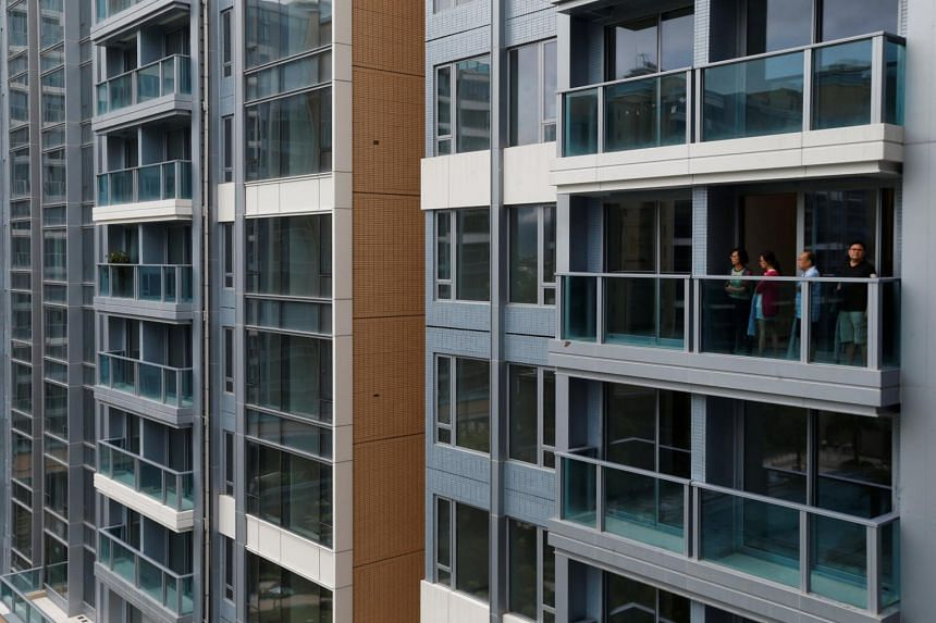 Visitors look from a balcony at a new flat in Park Yoho Genova, developed by Sun Hung Kai Properties, in Hong Kong, on July 3, 2017.