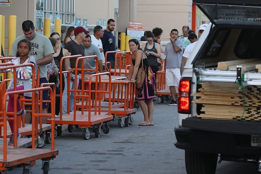 People waiting in line to buy plywood at The Home Depot as they prepare for Hurricane Irma on Sept 6, 2017, in Miami, Florida.