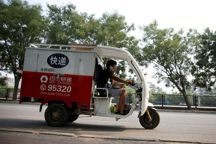A man rides an electric delivery vehicle of the Chinese logistics company Best Inc in Beijing.