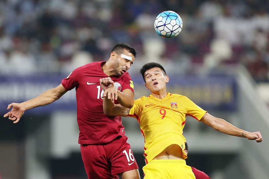China forward Xiao Zhi and Qatar's Boualem Khoukhi (far left) challenge for the ball during a World Cup qualifier. China won 2-1.