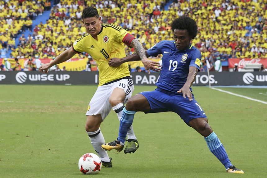 Colombia's James Rodriguez (left) and Brazil's Willian vie for the ball during the 1-1 draw in their World Cup qualifier on Tuesday. Willian volleyed home the game's opening goal in the first half.
