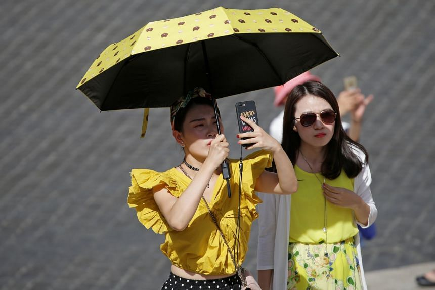Tourists shelter from the sun in downtown Rome, Italy, Aug 3, 2017.