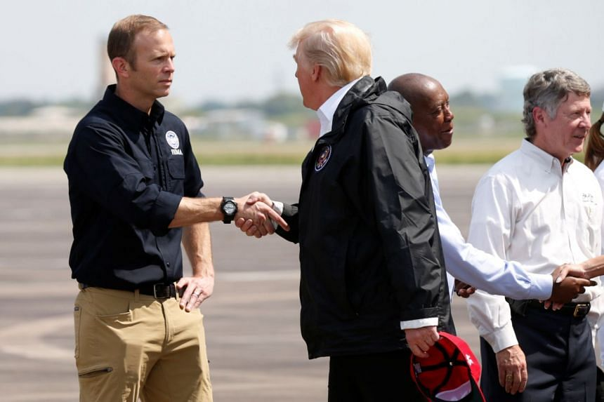 Brock Long greets US President Donald Trump on his arrival in Texas after Hurricane Harvey.