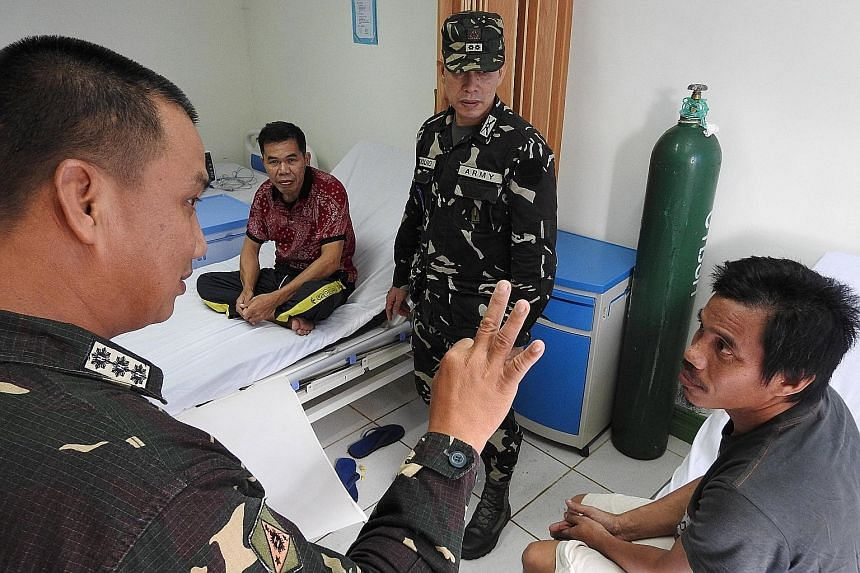 A Philippine military officer talking to the rescued Indonesians at a military hospital in Jolo, Sulu, yesterday. The two men were were taken by the Abu Sayyaf on Nov 16 last year as they were fishing in waters off Kunak, in Sabah, Malaysia.