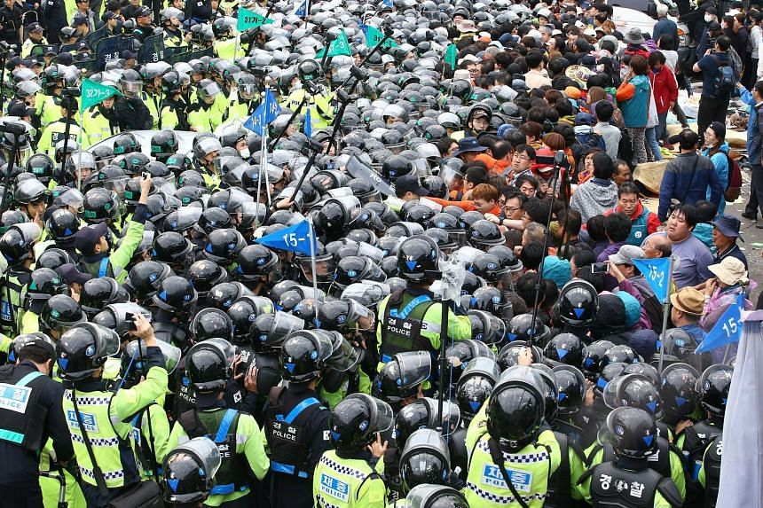Riot police clashing with protesters who tried to block trucks carrying Thaad launchers in Seongju, South Korea, yesterday.