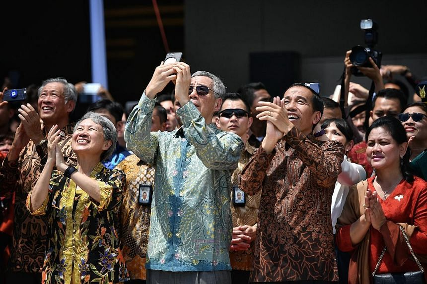 Prime Minister Lee Hsien Loong and President Joko Widodo viewing a joint fly-past by the Singapore and Indonesian air forces yesterday to mark 50 years of diplomatic relations, along with Mrs Lee and First Lady Iriana. Also present was Defence Minist