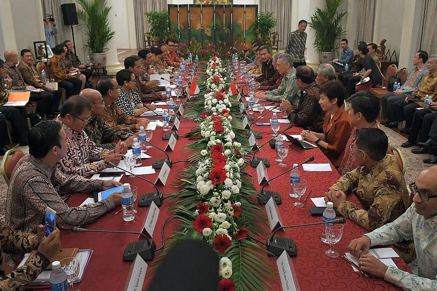 """The Indonesian and Singapore delegations, led by President Joko Widodo and Prime Minister Lee Hsien Loong, respectively, meeting at the Istana yesterday. The two leaders also held a """"four-eye"""" meeting. President Joko Widodo and Prime Minister Lee Hsi"""