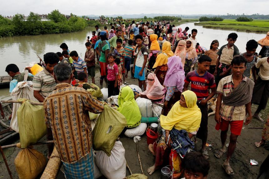 Rohingya refugees are seen waiting for a boat to cross the border through the Naf river on Sept 7, 2017.