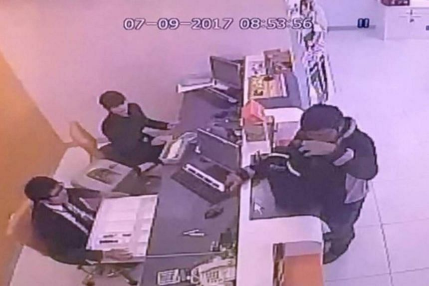 The armed robber was dressed in black and apologised to the bank teller during the heist.