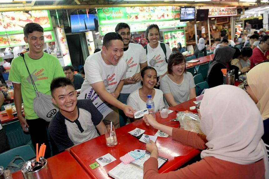 MP Amrin Amin (standing, second from left) and volunteers, including Hairul Marvin, 17, (left), giving out anti-drug collaterals to patrons at Simpang Bedok on Sept 9, 2017.