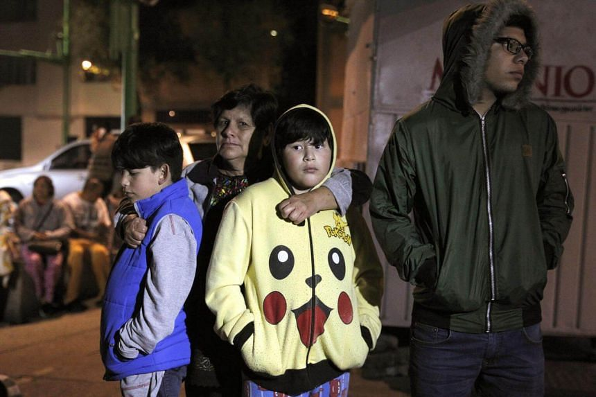 A family waits in the open in Mexico City after a 8.2-magnitude earthquake violently shook Mexico.