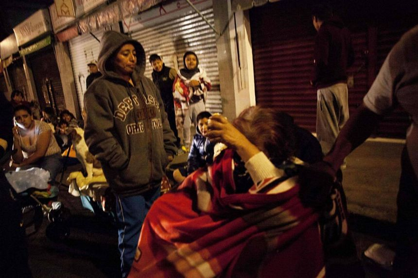 People gather on a street in the Tlatelolco neigbourhood of Mexico City during an earthquake on Sept 7, 2017.