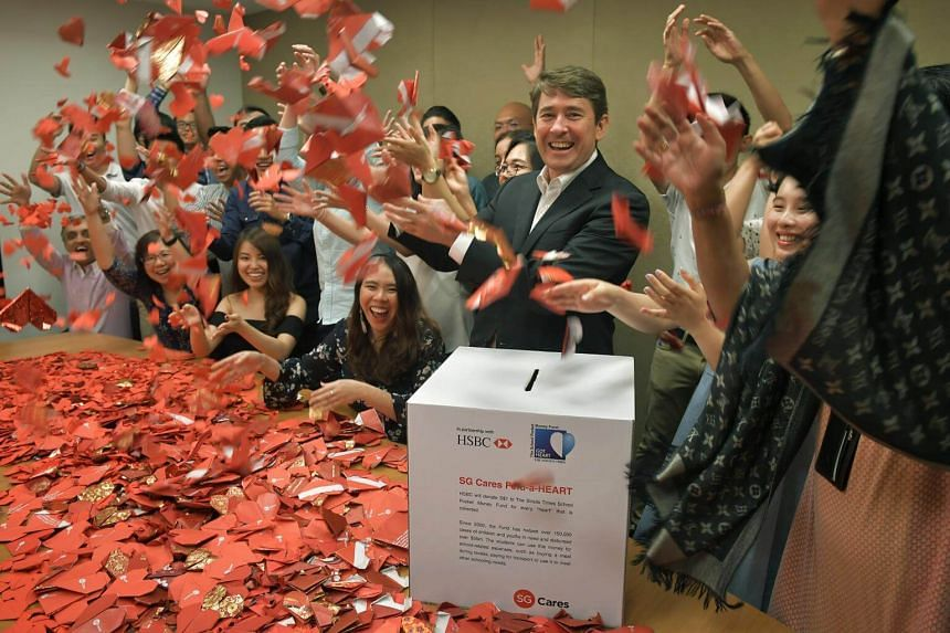 HSBC Singapore group general manager and  CEO Tony Cripps with staff and the origami hearts at HSBC building in Collyer Quay.