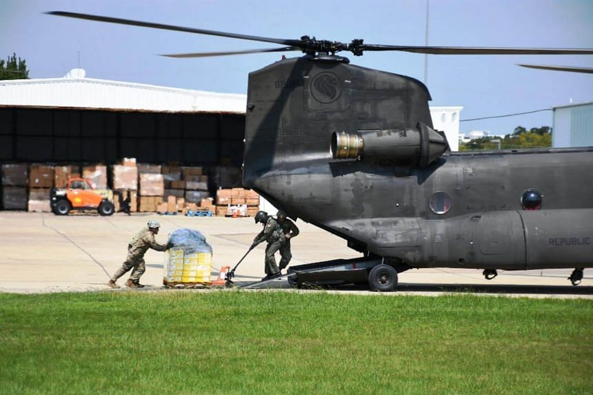 Airmen from the Republic of Singapore Air Force (RSAF) working closely with soldiers from the Texas Army National Guard (TXARNG) to load supplies onto the RSAF's CH-47 Chinook helicopter.