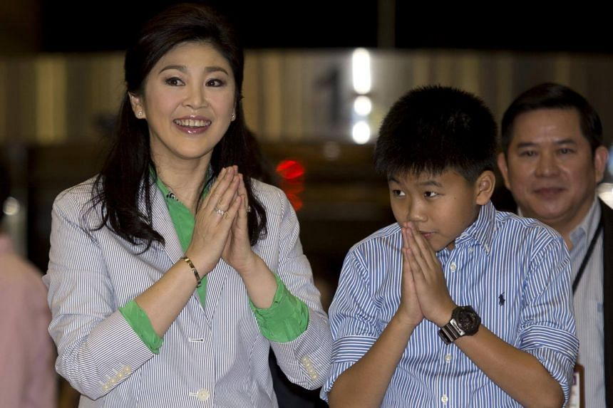 Thailand's deposed former prime minister Yingluck Shinawatra (left) and her son Supasek Amornchat gesture a traditional greeting to waiting media as they arrives at Suvarnabhumi International airport in Bangkok on July 23, 2014.