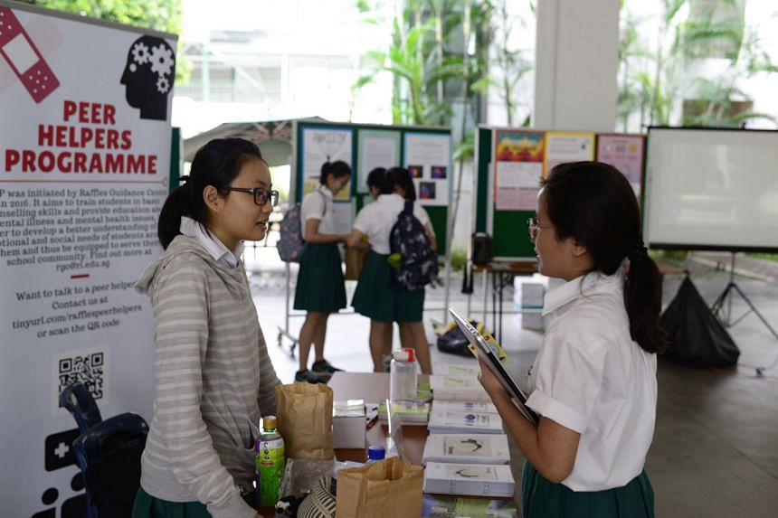 Year 5 student Jeanne Tan (left), 17, a peer helper, speaking to a student at a booth set up during the Mental Health Awareness Week held at Raffles Institution in August 2016.