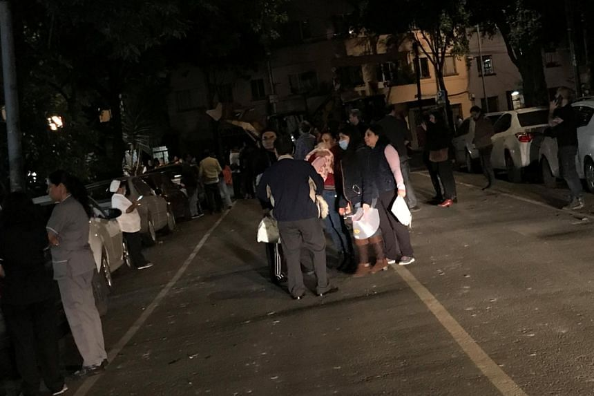 People gather on a street after an earthquake hit Mexico City on Sept 7, 2017.