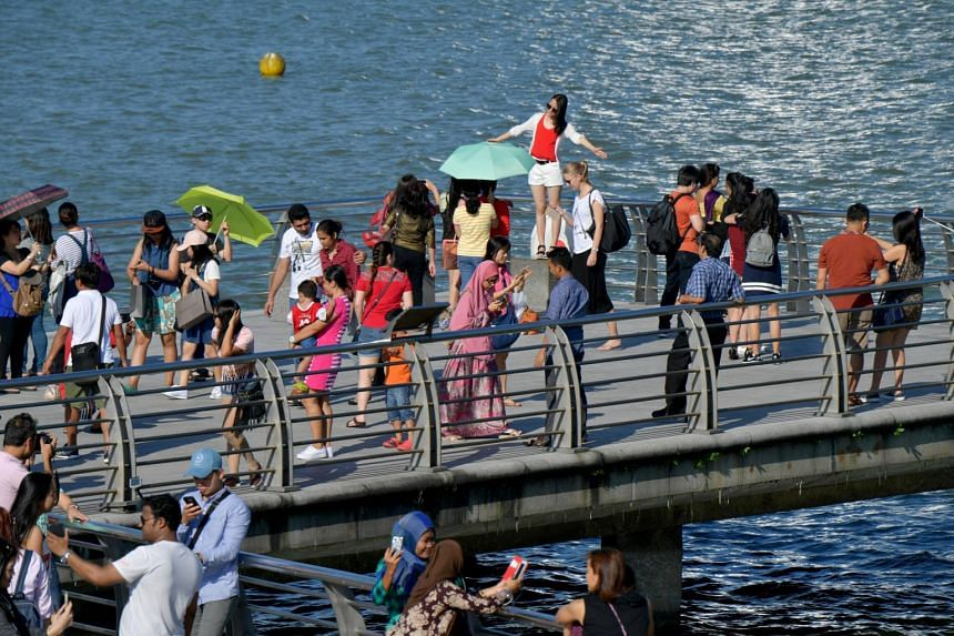 Tourists walking along Jubilee Bridge overlooking the Marina Bay area on June 4, 2017.