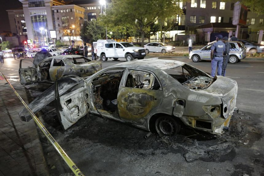 Two of the torched vehicles seen behind a police cordon after clashes broke out between metered taxi drivers and Uber drivers in Sandton City, in Johannesburg, South Africa, on Sept 7, 2017.