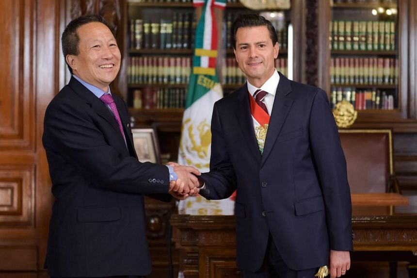 A handout file dated on June 20, 2016, provided by the Presidency of Mexico, shows the Mexican President Enrique Pena Nieto (right) greets the North Korean Ambassador Kim Hyong Gil (left) in Mexico City.