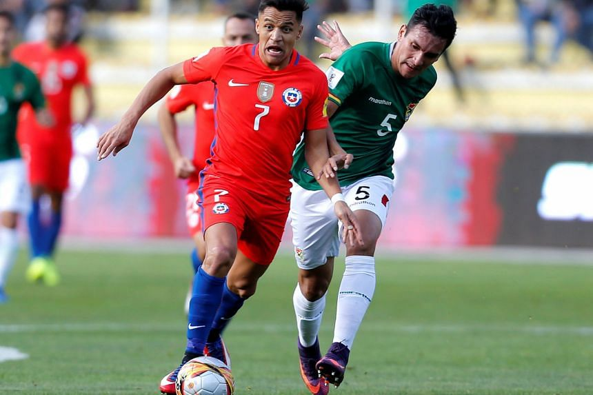 Alexis Sanchez goes past Bolivia defender Gabriel Valverde during Chile's 1-0 loss in the World Cup qualifier. The Arsenal star, whose move to Manchester City did not materialise, is not yet fully fit but Gunners manager Arsene Wenger expects him to