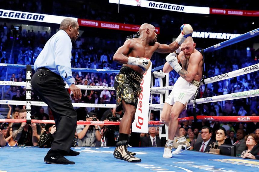 Floyd Mayweather has Conor McGregor on the ropes before winning their fight by a technical knockout in the 10th round. The victory gave the American a landmark 50-0 career record.