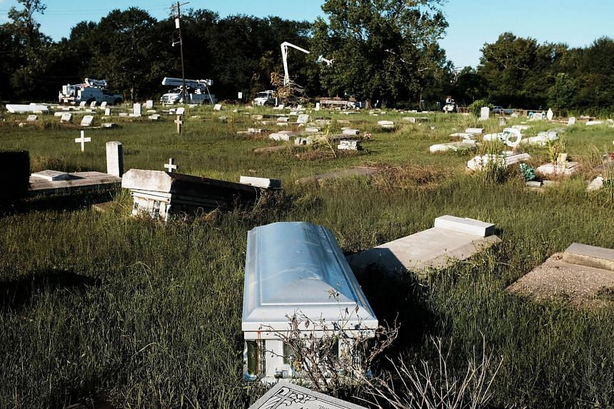 A coffin uprooted by floods lies in a cemetery in Orange, Texas, Sept 7, 2017.