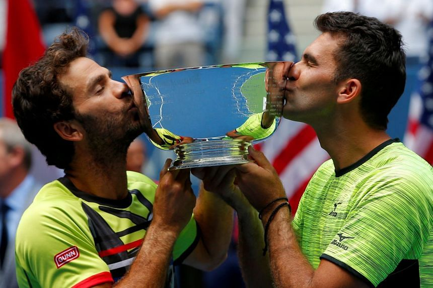 Jean-Julien Rojer of the Netherlands (left) and Horia Tecau of Romania kiss the winners' trophy.