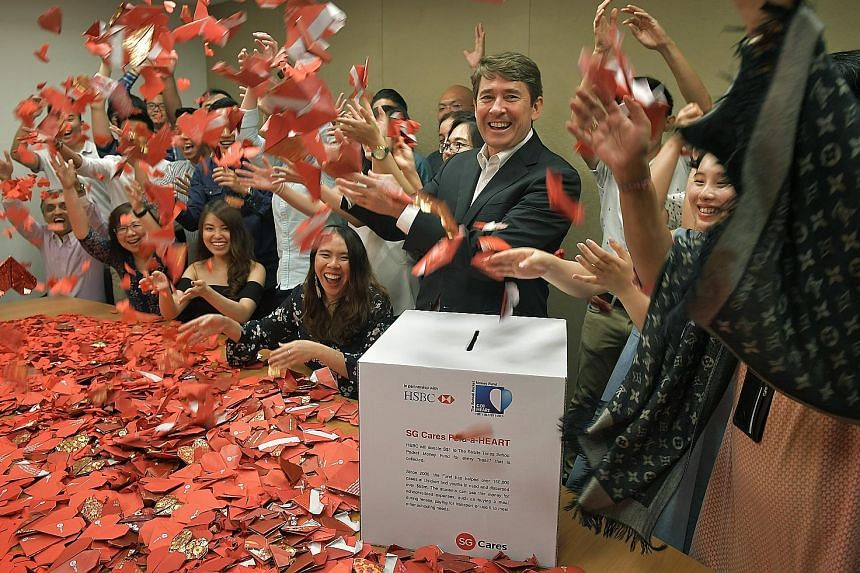 HSBC Singapore's group general manager and chief executive officer, Mr Tony Cripps, and his staff folding the last origami hearts yesterday for the Fold-A-Heart campaign, in which the bank gave $1 to the ST Pocket Money Fund for each folded heart col