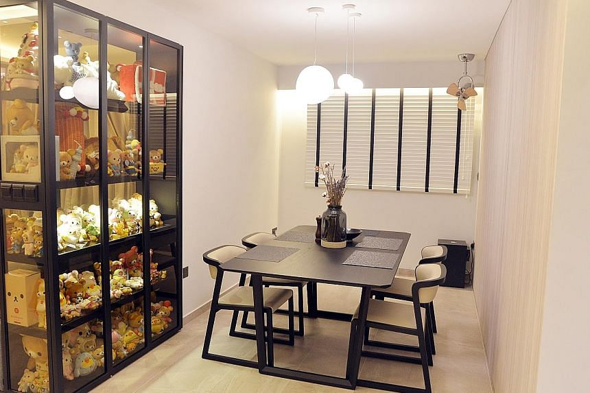 A tinted glass cabinet with black leather laminates not only showcases Mrs Sarah Lim's teddy bear collection, it also acts as a divider between the living and dining areas. The master bathroom has a rain shower with an LED ring light installed as the