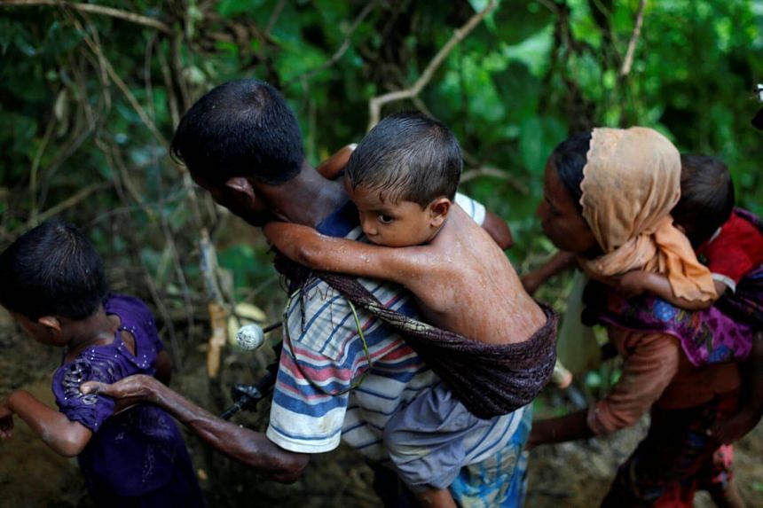 Rohingya refugees climb up a hill after crossing the Bangladesh-Myanmar border in Cox's Bazar, Bangladesh on Sept 8, 2017.