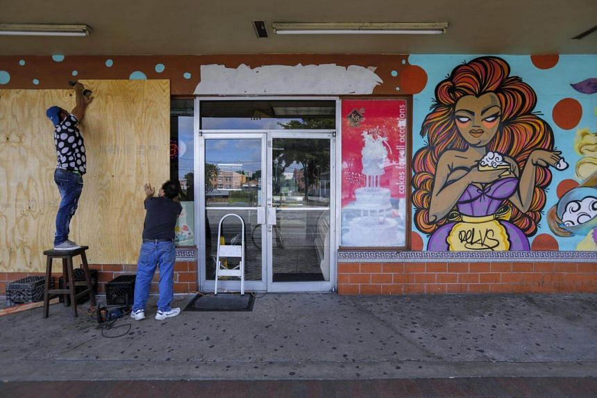 Workers put plywood over the windows of Yisell Bakery on Calle Ocho in the Little Havana neighborhood ahead of the expected arrival of Hurricane Irma in Miami, Florida, USA on Sept 8, 2017.