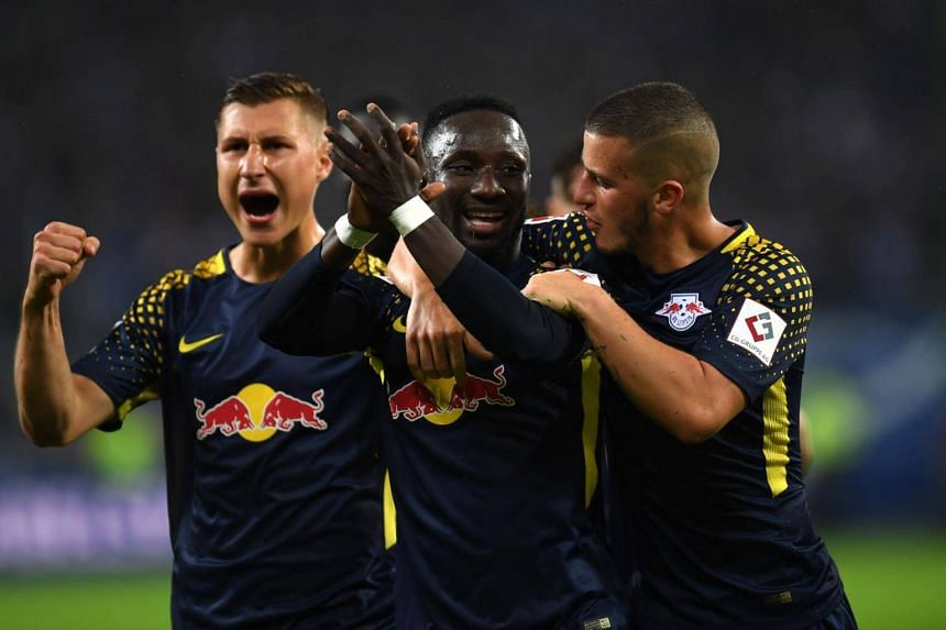 Leipzig's Guinean midfielder Naby Keita and his teammates celebrates after scoring during German first division Bundesliga football match between Hamburger SV and RB Leipzig in Hamburg on Sept 8, 2017.
