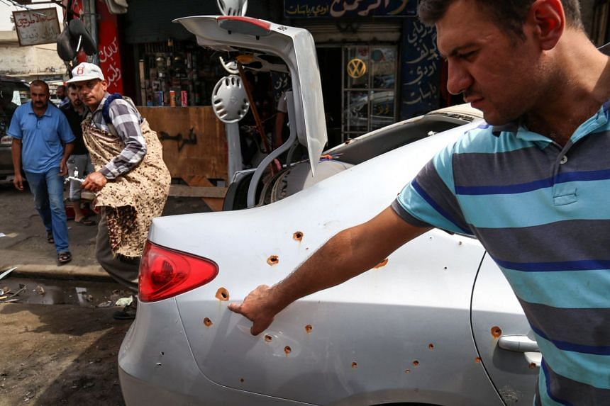 An Iraqi points at the bullet-riddled body of a car damaged during the offensive to retake Iraq's second-largest city from ISIS.