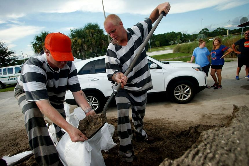 Inmate trustees from the Brevard County Jail work to fill and load sandbags for residents as people in the area prepare ahead of Hurricane Irma on Sept 7, 2017 in Meritt Island, Florida.