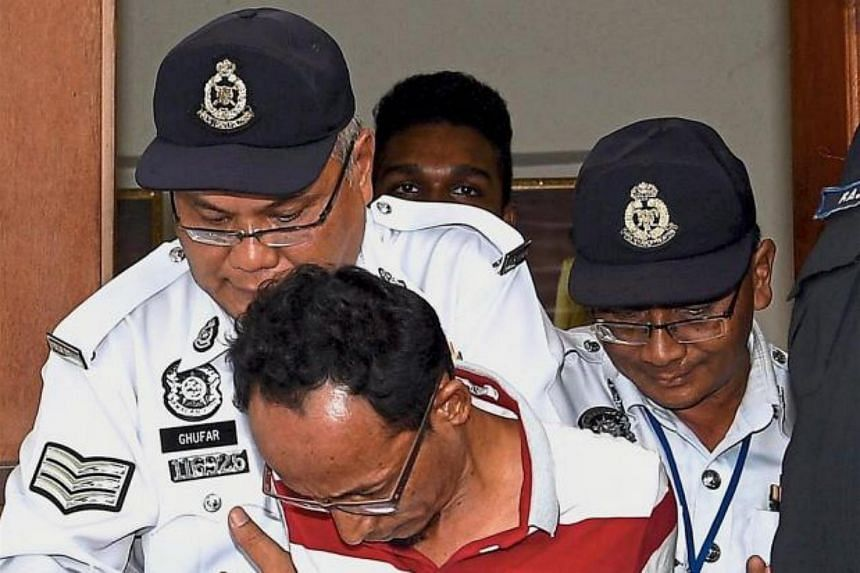 Police officers escorting  businessman Anuar Wahab, 46, to the magistrate's court in Kuala Selangor where he was charged with dangerous driving and causing an accident at the Kuala Lumpur-Kuala Selangor (Latar) highway.