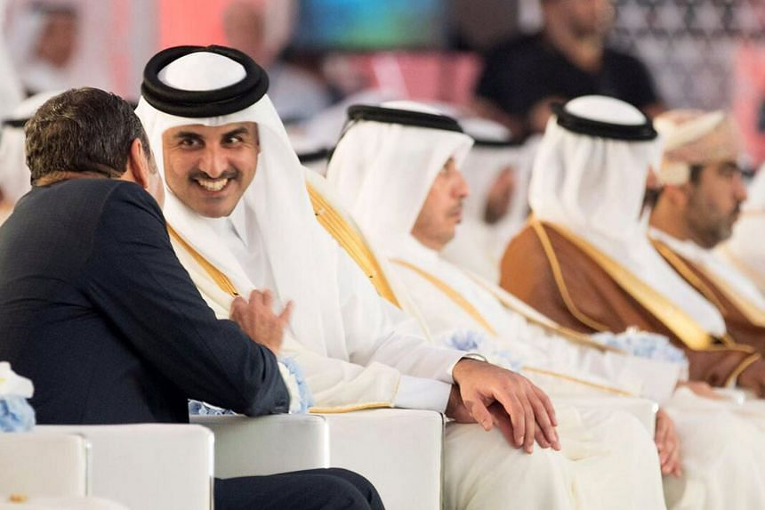 Qatar's emir, Sheikh Tamim bin Hamad Al-Thani  (2nd from left), talking to an unidentified man during the inauguration of the new Hamad Port in Doha on Sept 5, 2017.